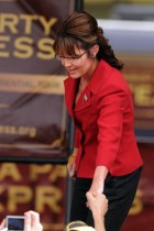 Sarah shakes hand of someone in audience at TPX rally in NH