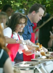 Sarah smiles as she puts BBQ on plate of attendee at Kirk Adams rally