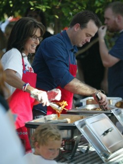 Sarah smiles at attendee as she and Kirk Adams serve BBQ