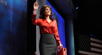 Sarah waves as she walks onstage at CPAC 2012