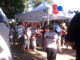 Shot from distance of Sarah serving BBQ under tent at Kirk Adams rally