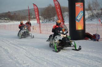 Team 11 towing across finish line at 2012 Iron Dog