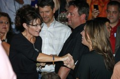 Todd watches as Sarah clasps hand of young woman at C4P meetup in Iowa