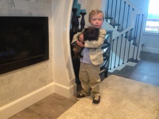 Tripp in Sunday School clothes holding puppy