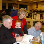 Chuck Heath Sr and Jr sign books while Mrs. Heath and Chuck Jr's daughter look on