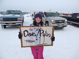 Piper holds up Go Team 11 sign at Iron Dog 2013 Finish