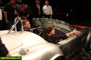 Sarah and Todd sitting in roadster at Collector Auto Auction in Scottsdale Arizona