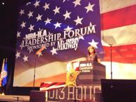 Sarah at podium at NRA-ILA Leadership Forum on flag in background