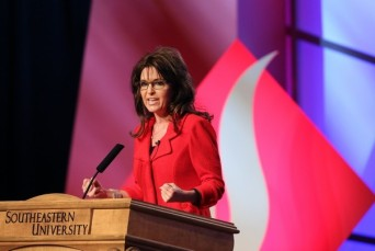 Sarah gestures with clenched fists at SEU leadership forum