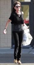 Sarah in black top and skinny jeans emerging from KMart in Studio City CA