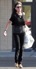 Sarah in black top and skinny jeans emerging from KMart in Studio City CA