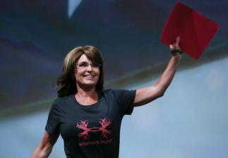 Sarah raises notebook as she approaches podium at 2013 NRA Convention
