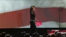 Sarah waves as she approaches podium at 2013 NRA Convention
