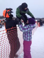 Todd hands Trig over fence to Piper before start at Iron Dog Race 2013