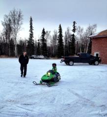 Todd walking toward Tripp on snowmachine