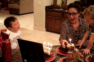 Trig laughing as Bristol holds cake with lit candle