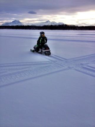 Tripp makes an X in the snow as he rides his snow machine
