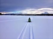 Tripp riding his snow machine toward camera