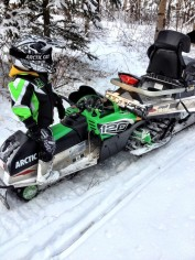 Tripp standing beside his Arctic Cat snow machine